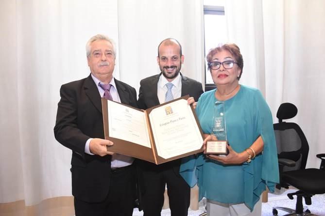 El concejal Santiago Jaramillo Botero hace entrega de reconocimiento al dueño del restaurante Crispino Pizza y Pasta y su esposa.
